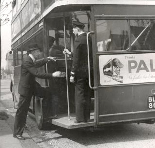 Private: Passenger boarding double-decker bus in London, England